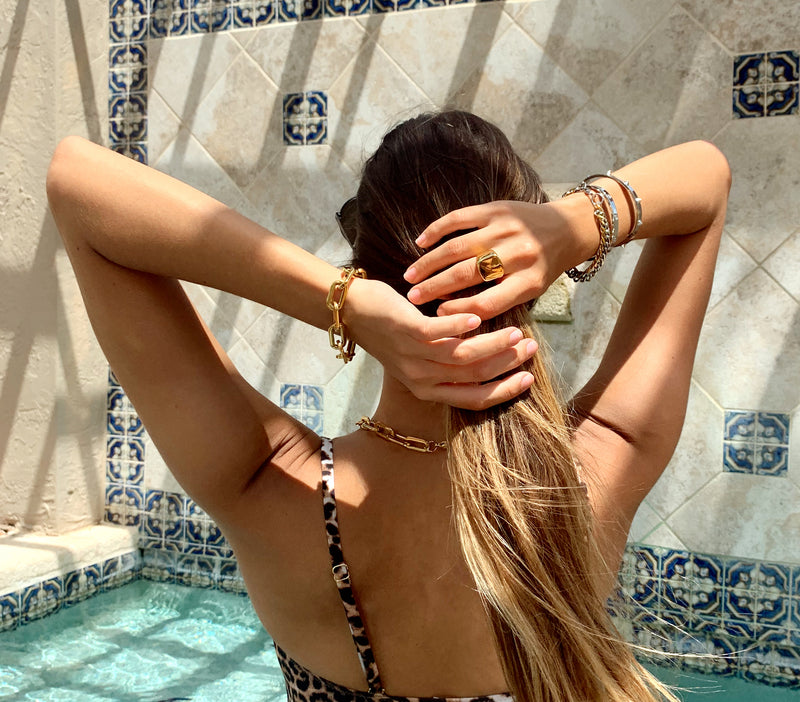 Model wearing the Puerto chain bracelet in Gold, Forever Ring gold, spike bangles, crystal bangle and palma bracelet.