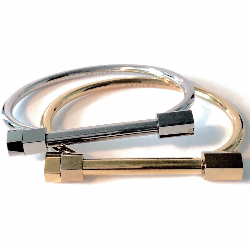 Weight bangles in Gold plated, Rhodium plated stainless steel. It's a plain bangle with a bar design that serves as a lock for the bangle.