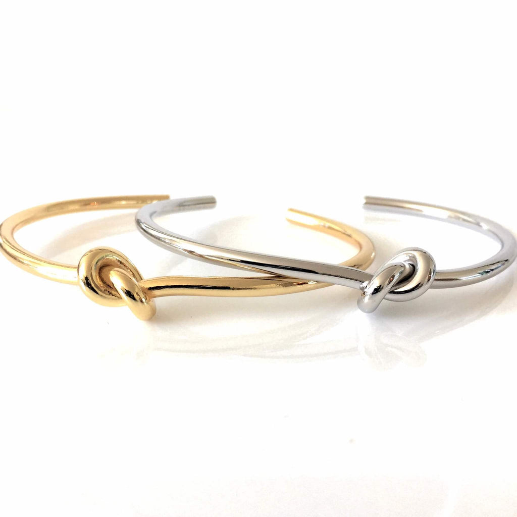2 Knot bangles which are open bracelets in gold and silver with a knot design in the center.