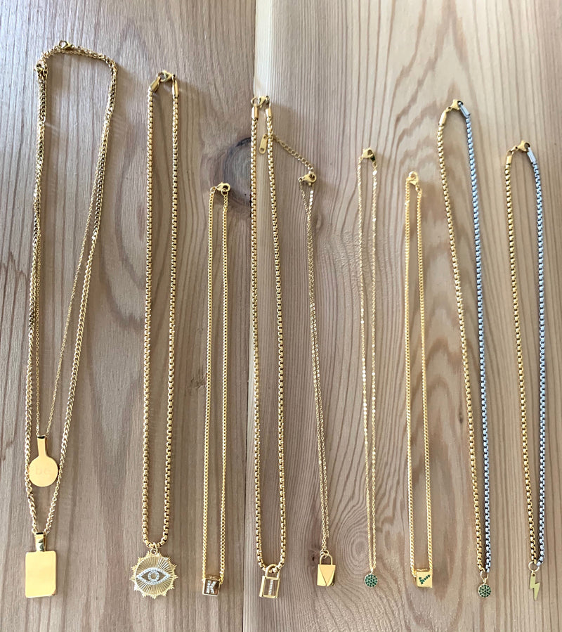 9 necklaces on a wooden background. From the left is two piece layered gold necklaces with circle and rectangular pendants, the I SEE NECKLACE, gold necklace with initial pendant, 2 gold necklaces with lock charm, gold necklaces with green dot and square with checkmark, half gold and silver necklace with green dot pendant and the last necklace is half gold half silver chain with the lightning bolt pendant.