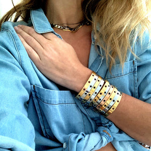 Model wearing 10 Osa Mayor bangles. Stainless Steel Bangle Bracelet in Gold Plated, Rhodium Plated, Rose Gold with stars design.