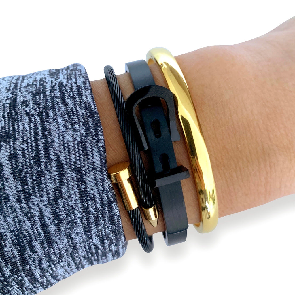 Model wearing THE BLACK STACK which comes with the plain bangle in gold, tornillo bangle in black with gold details and the belt bangle in black.
