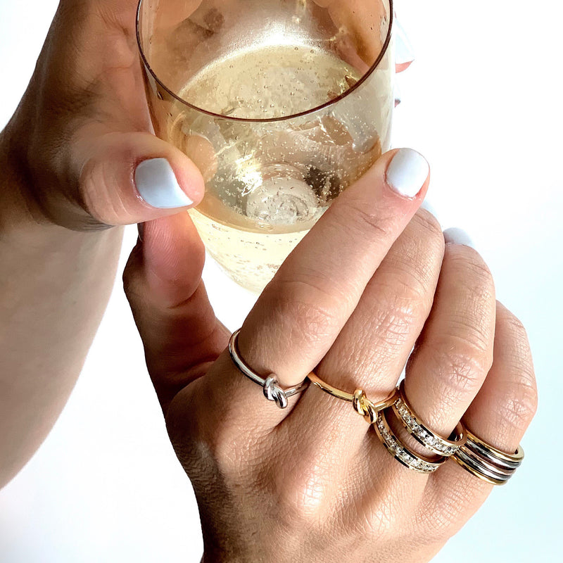 Model's hand holding a Champagne glass wearing the knot rings in silver and gold, square rings in silver and gold.