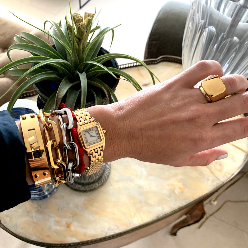 Model wearing the Forever Ring in Gold. She is wearing a gold watch, two Puerto Chain bracelets in gold and silver and the Belt Cuff Medium in Gold.