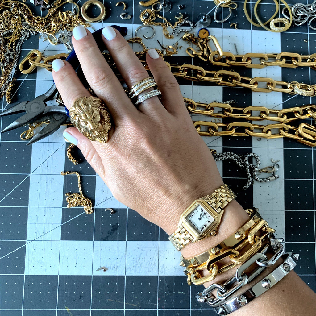 Model wearing the Lion Ring and SQUARE ZIRCONIA DOBLE in Silver and Gold. She is also wearing a gold watch, two PUERTO CHAIN BRACELET in Stainless Steel Rhodium Plated and Gold Plated Chains, Crystal bangle in Silver and Spike bangle in Silver.