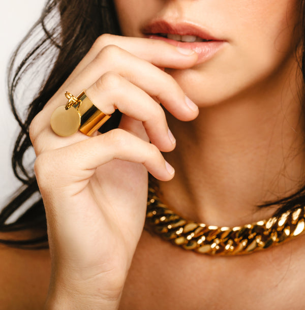 Model with her hands on her chin wearing the Coin Ring which is gold around one inch wide with a knob that has a coin charm hanging on it. She is also wearing the palma necklace in Gold.