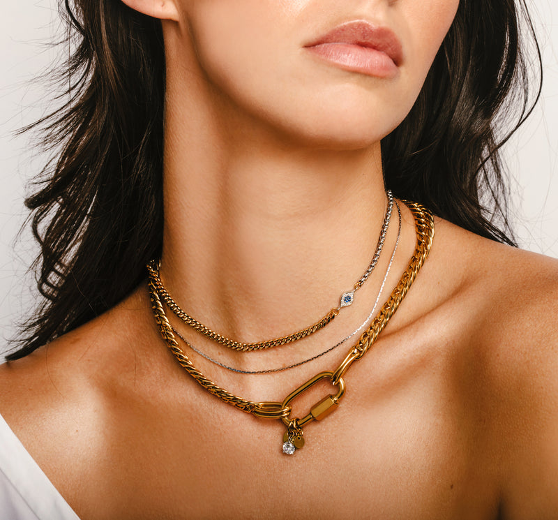 Model wearing the Maya Necklace, 18k Gold plated Stainless steel chain 3  Layered chain set with one thin gold chain, half gold and half silver chain with Zirconia evil eye and a thicker gold chain with oval lock.