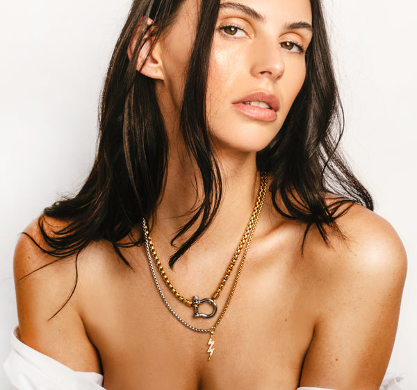 Model wearing the Herradura Thunder which comes with two necklaces, one is the Herradura necklace in gold chain and silver clasp and the other is a half gold and half silver long chain with the lightning bolt pendant.