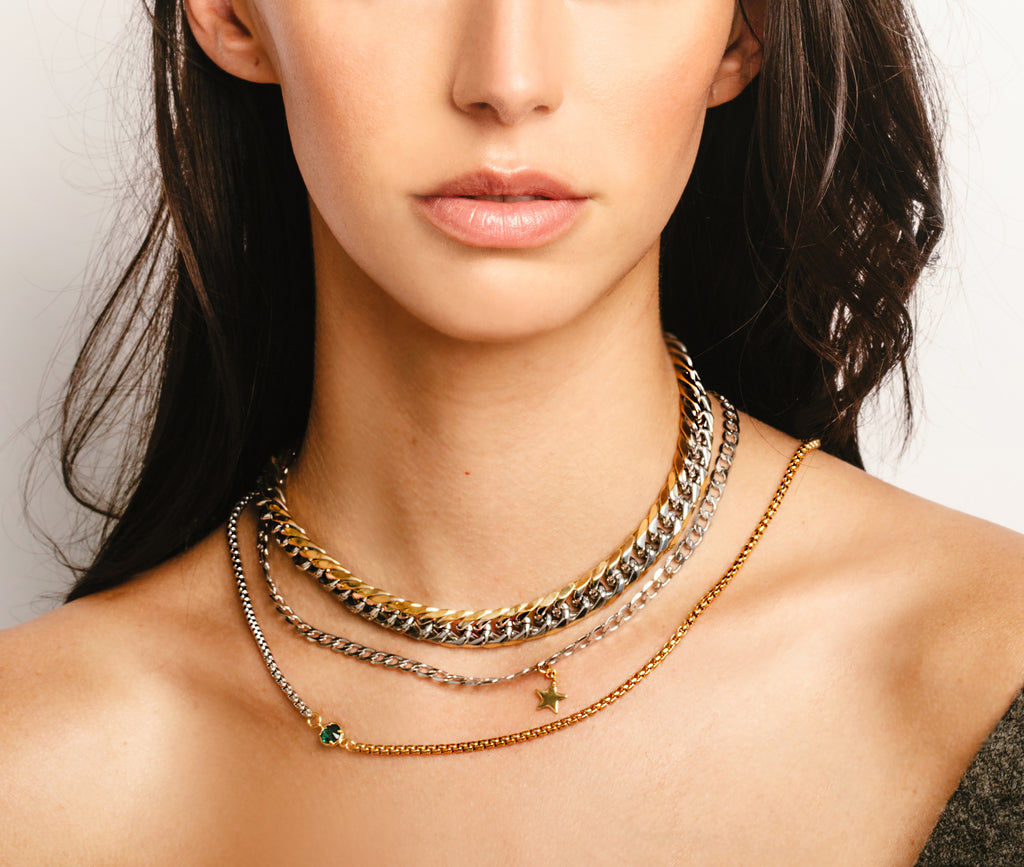 Model wearing the 3 piece Emerald and Mix set which comes with a half gold and half silver thin chain with green emerald stone in the center, silver chain with star pendant, and chunky Mix chain which is a mix of gold and silver.