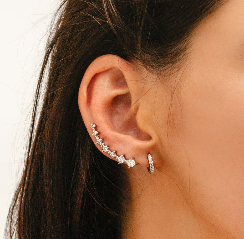 Model wearring the Climbing earring on her right ear together with a small hoop earring. The Climbing earring is a long silver crystal clip earring covering almost the half part of the model's ear.