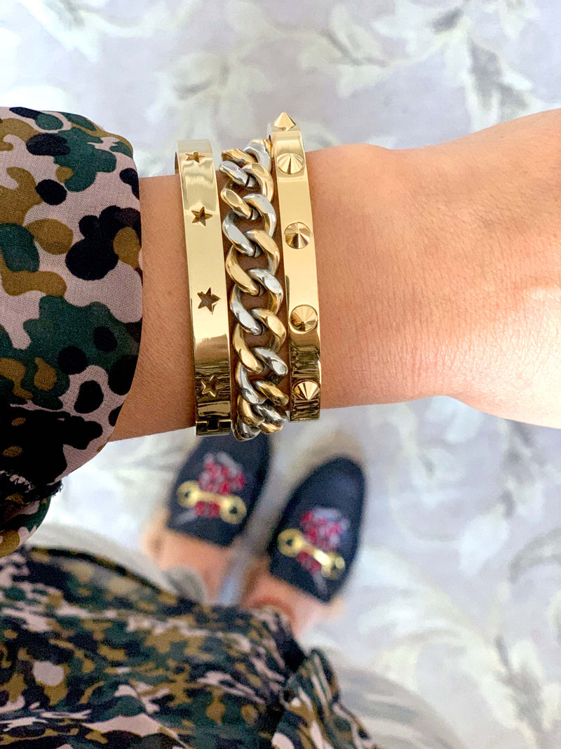 Model wearing the the Sila Stack which comes with three bracelets. One is the gold spike bangle, mix chain bracelet and the shooting stars bangle in gold.