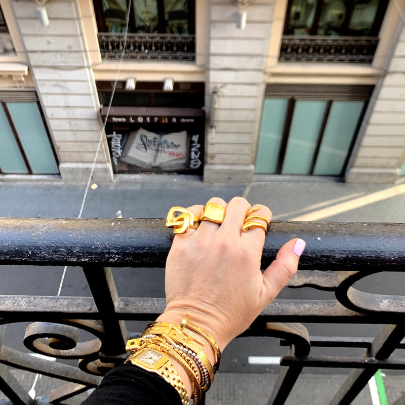 Model wearing a Buckle ring, Forever ring and Cascabel rings in gold. She is also wearing a gold watch, Puntitos bracelet, belt bangle and Clavo Shini bangle in gold.