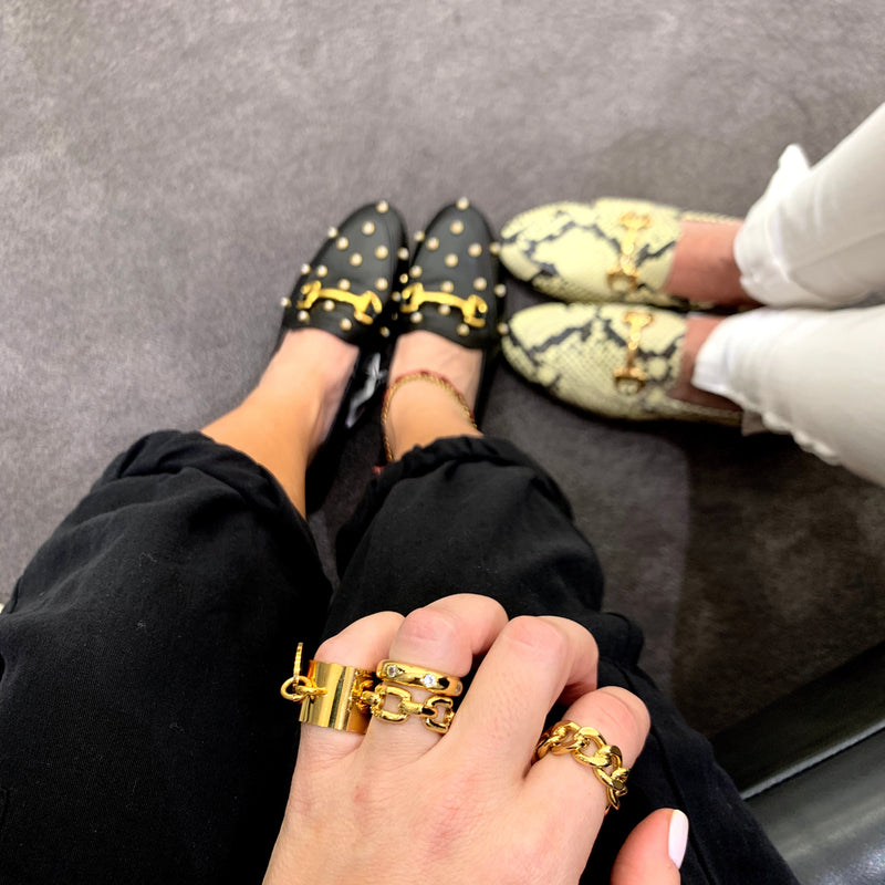 Model's right hand accessorised with the Coin Ring, Chain ring, Link and crystal rings. it shows her shoes in black with gold dots and details. it shows another woman standing beside her wearring a white pants and leopard designed shoes with gold details.