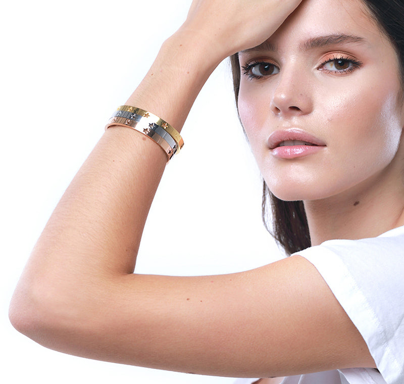 Model wearing Three Osa Mayor bangles. Stainless Steel Bangle Bracelet in Gold Plated, Rhodium Plated, Rose Gold with stars design.