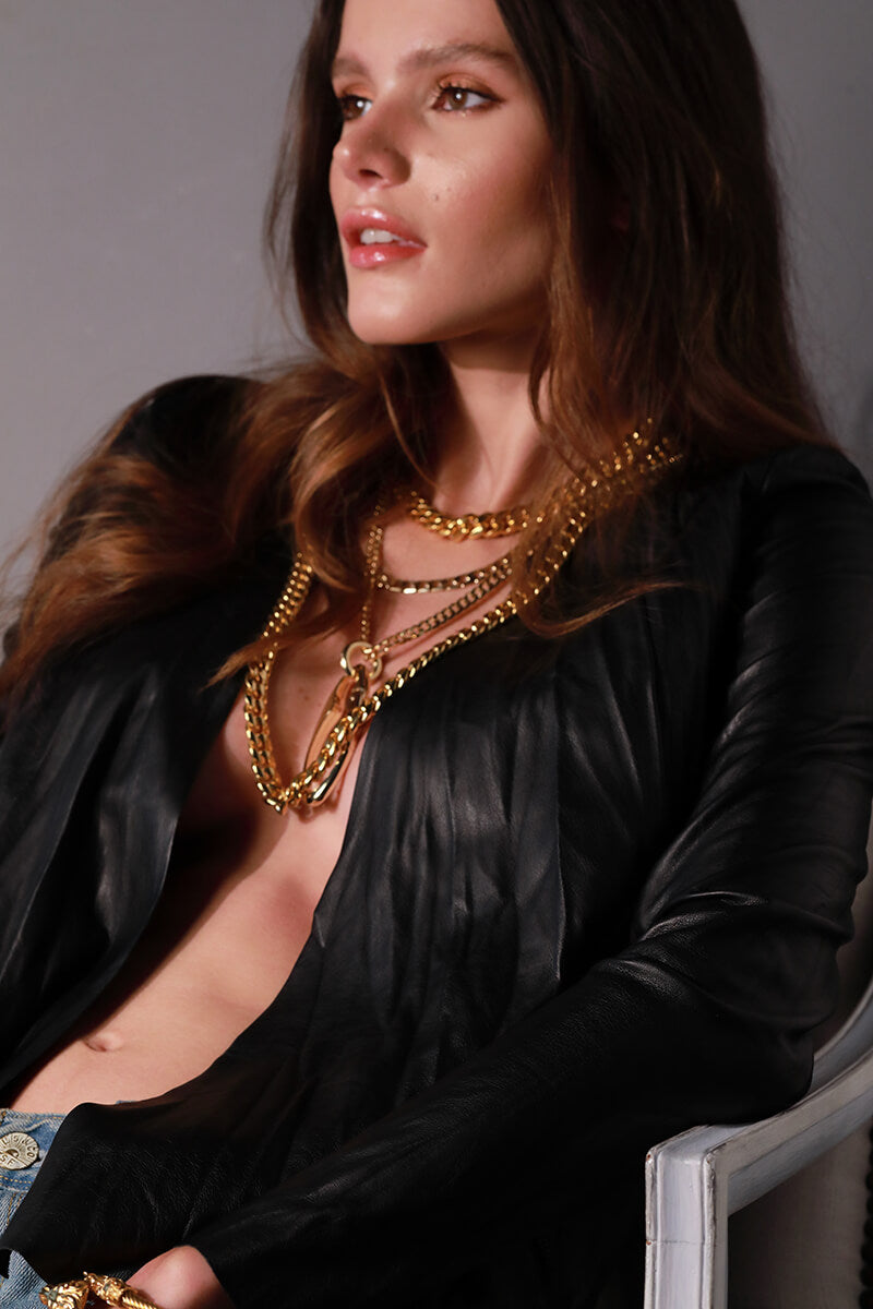 Model sitting in a chair in black longsleeves wearing the Palma Necklace which is a thick chain made of Gold plated Stainless steel with box lock and the Palma chain bracelet. She layered it with three other chain necklaces that are all in gold.