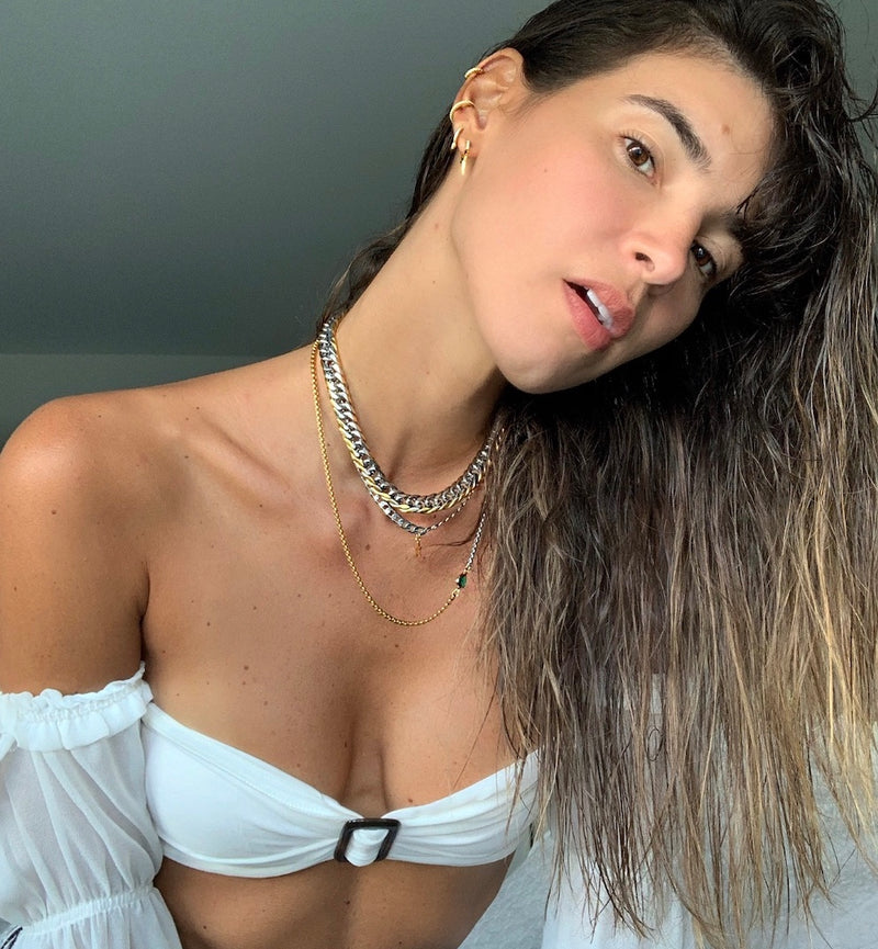 Model wearing a white bralette with puff sleeves accessorised with the 3 piece Emerald and Mix set which comes with a half gold and half silver thin chain with green emerald stone in the center, silver chain with star pendant, and chunky Mix chain which is a mix of gold and silver and also the Ear party set in gold.