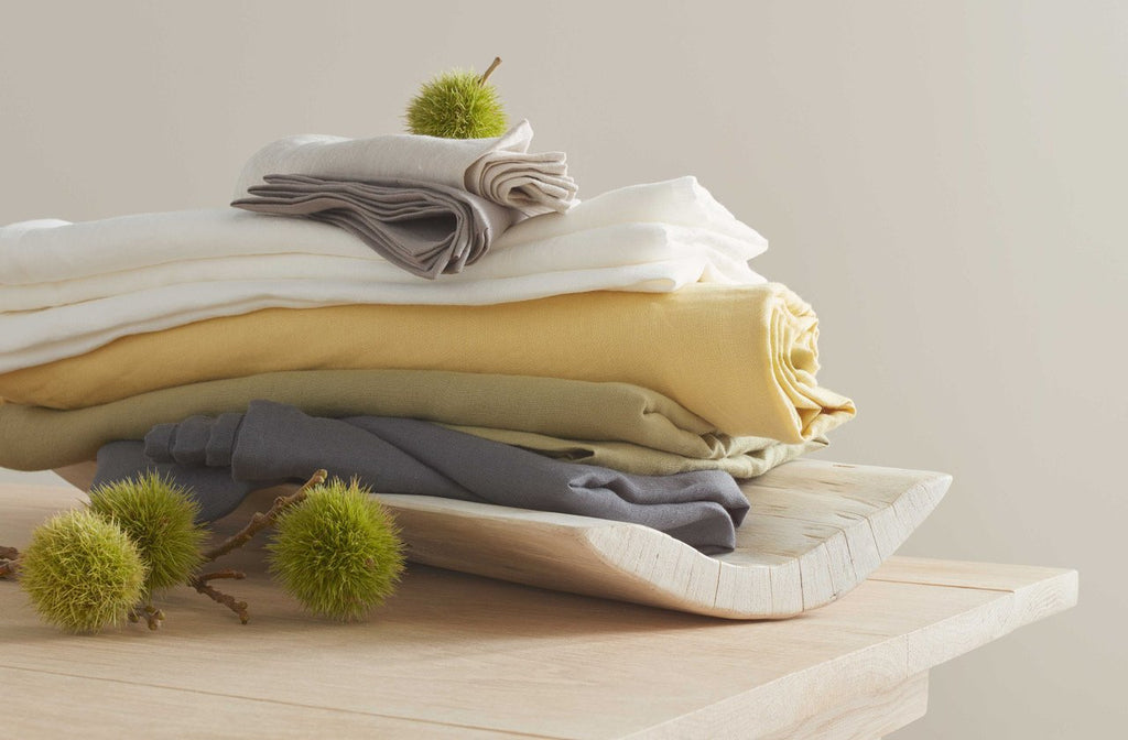 Stack of Embrin tablecloths in different solid colors