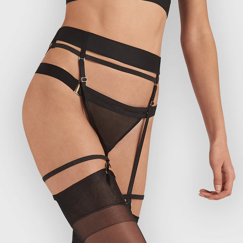 Woman wearing a black suspender belt which cinches the waist & flatters her silhouette. Paired with a Hale black thong.