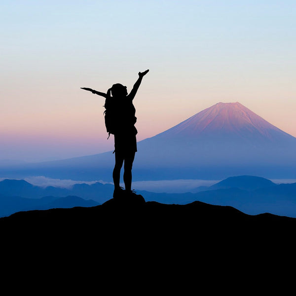 woman standing atop a mountain peak