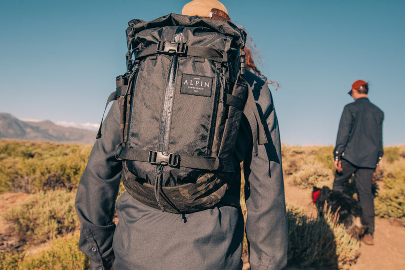 closeup of a backcountry backpack as two friends hike in the mountains