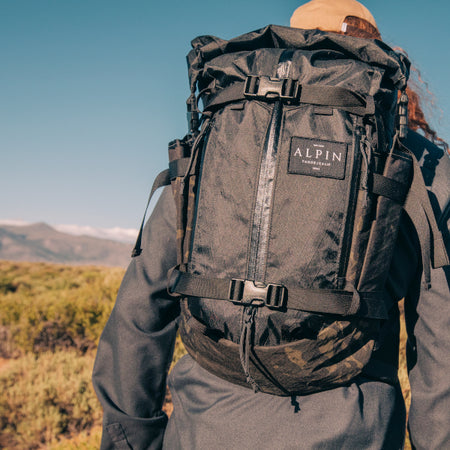 hiker wearing alpin backpack eyes nearby mountains