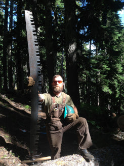 man standing next to crosscut saw