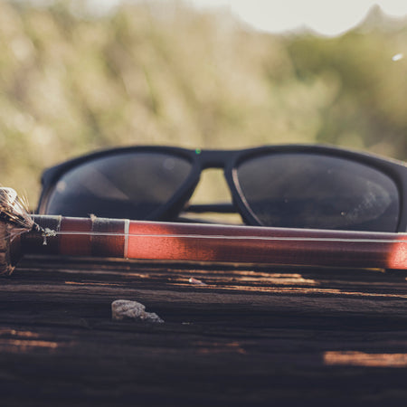 a pair of black sunglasses sitting on a log next to a fly rod