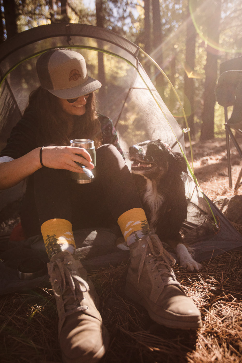 woman sitting near her tent with her pup