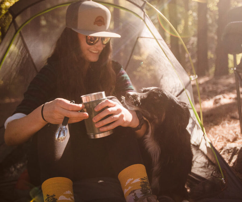 girl sitting in front of her tent with her pup looking up at her