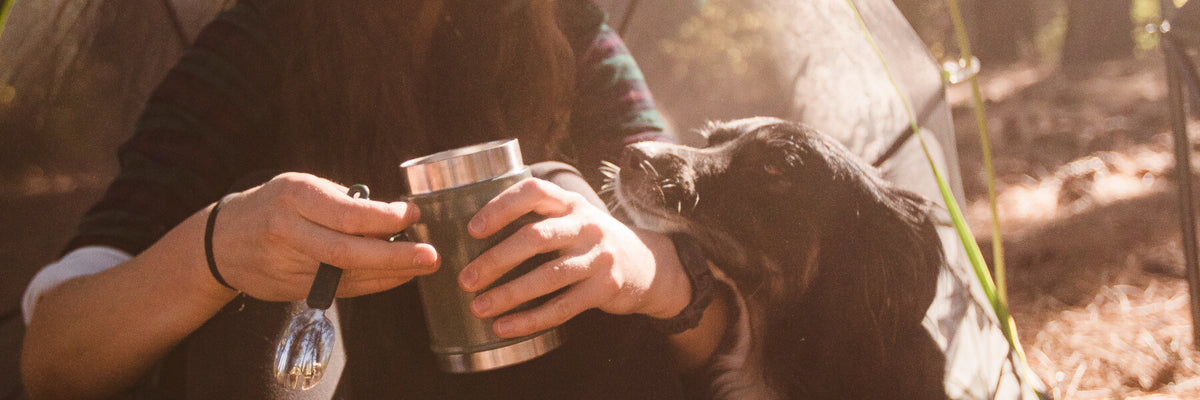a girl holding a food jar sitting next to her dog
