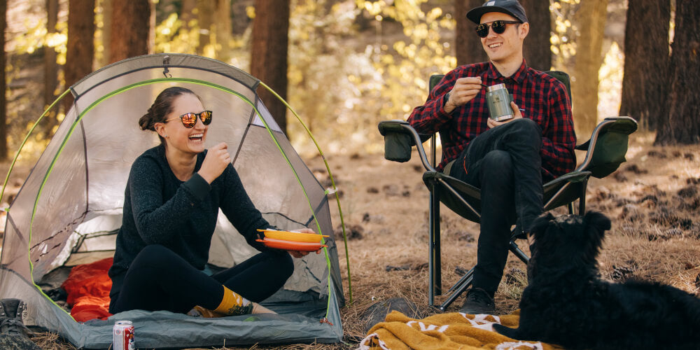 a woman and man eating at their campsite