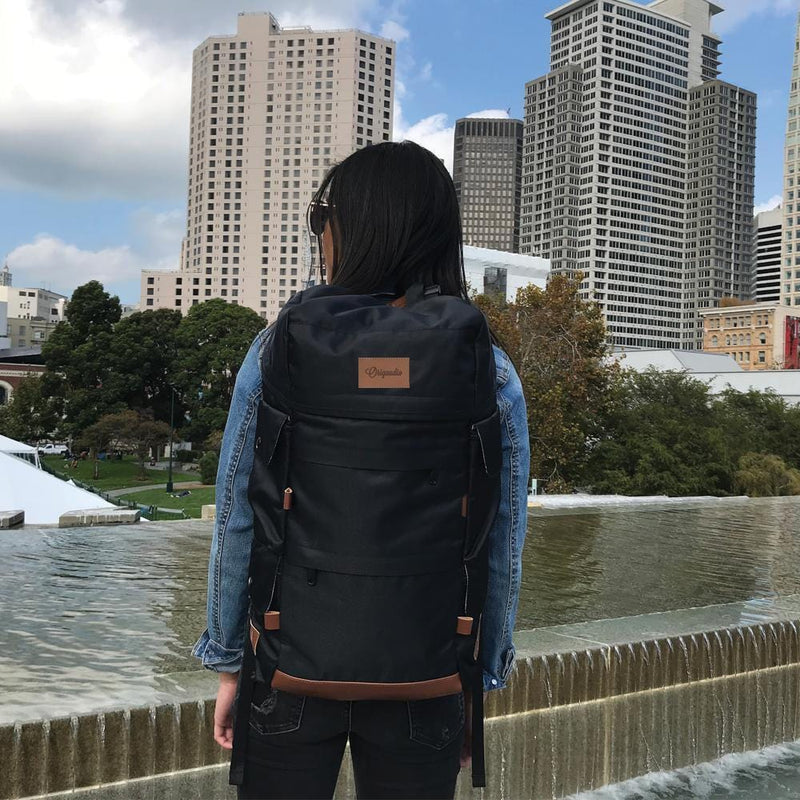 A woman carries the Black Presidio Pack through the city.
