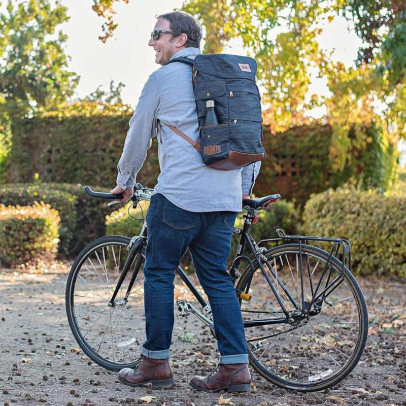 A man wears the Denim Presidio Pack while walking his bike.