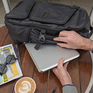 A man pulls a laptop out of the Tahoe Weekender Pack.