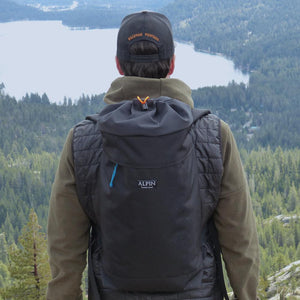 A man wears the Crag Pack overlooking a lake.