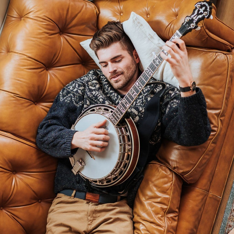 A man wears the Grip6 Men's Craftsman Olive Belt while playing the banjo.