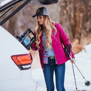 A woman wears the Grip6 Women's Sego Lily Belt while preparing to cross country ski.