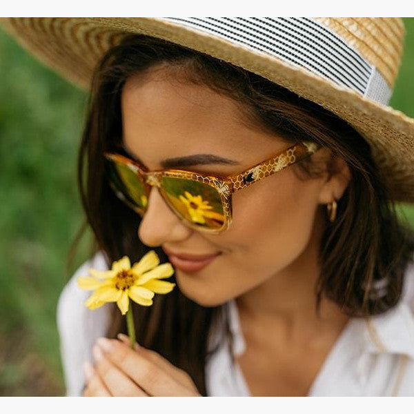woman smelling a daisy in a straw hat wearing sunglasses