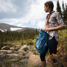 Load image into Gallery viewer, A woman carries the DL16 Backpack in the woods.