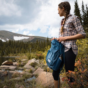 A woman carries the DL16 Backpack in the woods.
