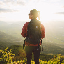 Load image into Gallery viewer, A woman stands on a cliff wearing the Beast28 Technical Backpack