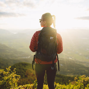 A woman stands on a cliff wearing the Beast28 Technical Backpack