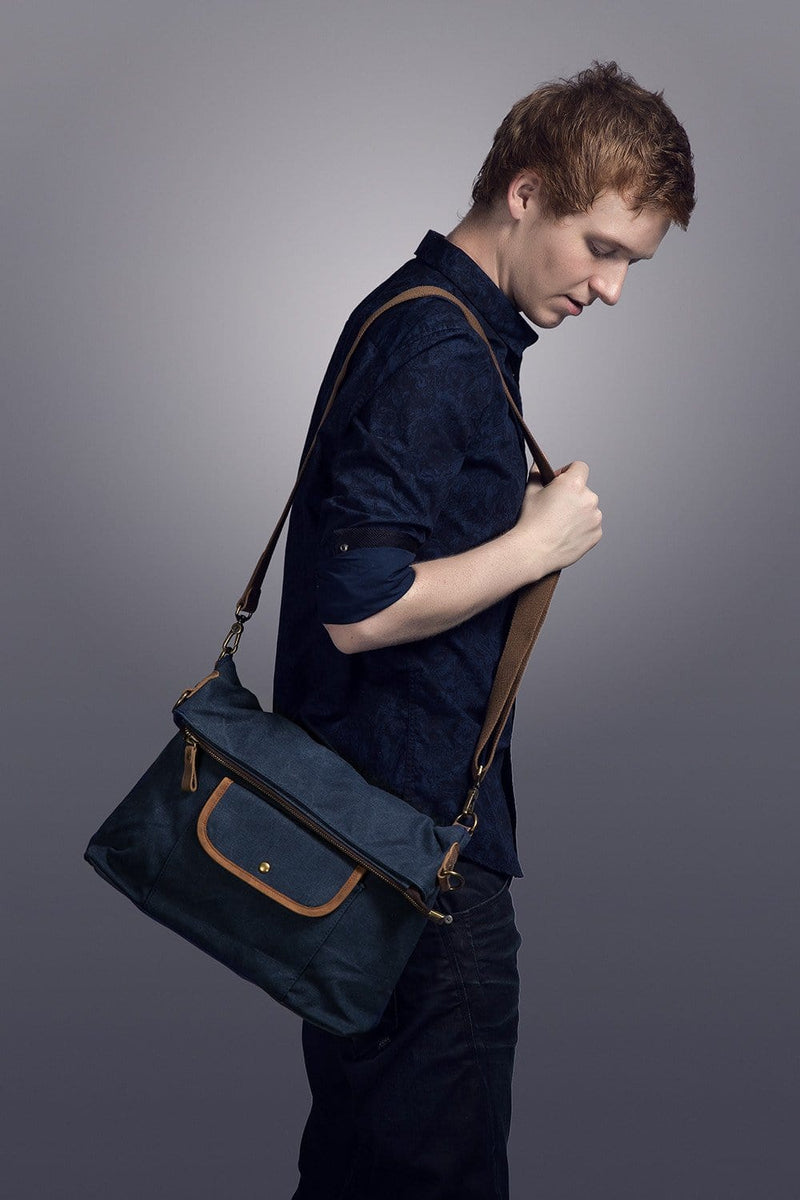 A man carries the Hobo Canvas Messenger Bag.