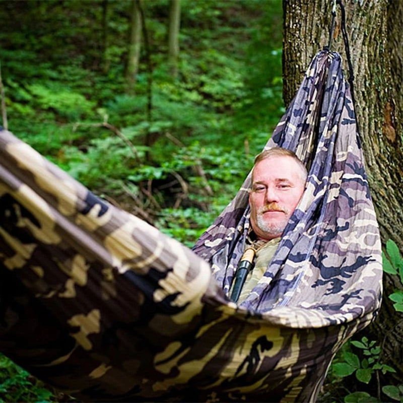 comfortable looking mans face pokes out of a camouflage hammock in the forest