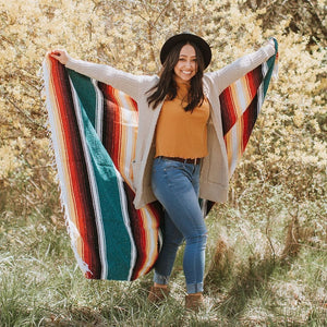 woman smiling while holding monterey blanket in outstretched arms
