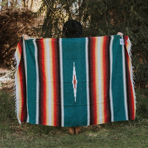woman holding up blanket against her back