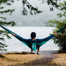 Load image into Gallery viewer, man stretched out sideways in a hammock looking towards a lake