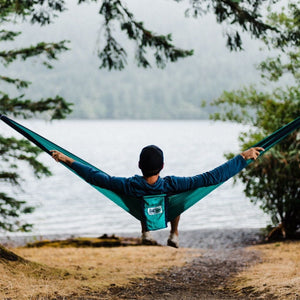 man stretched out sideways in a hammock looking towards a lake
