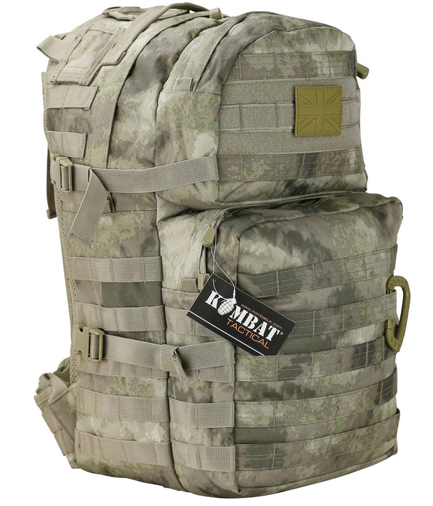 "front image of medium sized beige backpack with dark brown and green ""smudged ""into it. with 2 front compartments. velcro panels are across the top and molle attachments across the bottom one. 2 side compession straps also visible"