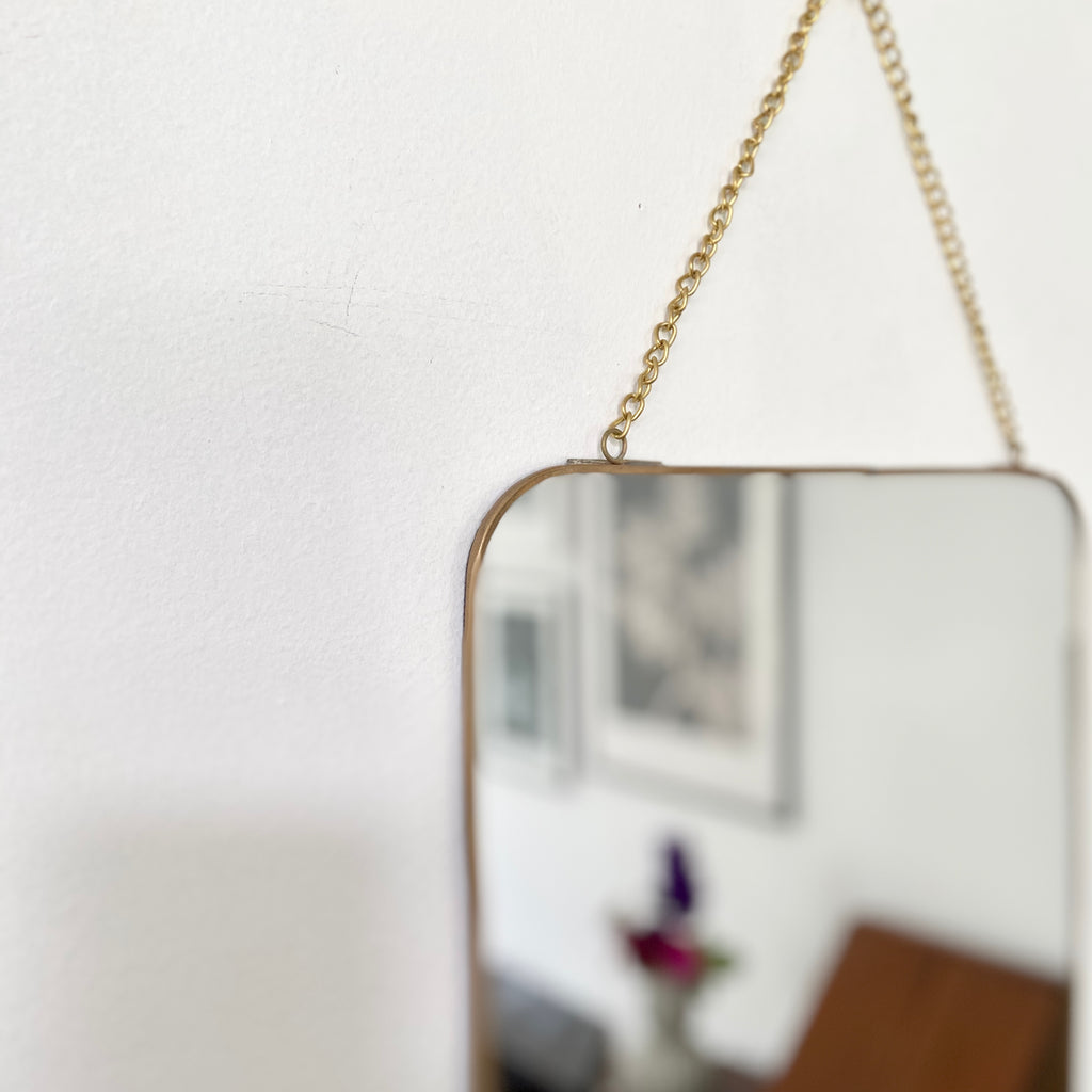 detail of brass chain on brass mirror